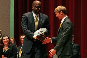 Rodney Bennett presents Brandon Baker with a plate commemorating his acceptance into the Student Hall of Fame Thursday afternoon in Bennett Auditorium.  Zachary Odom / Printz