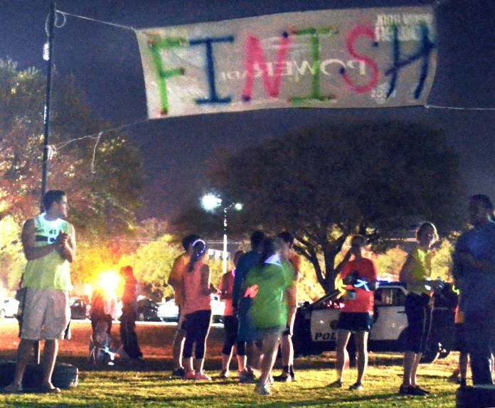 Onlookers cheer racers as they finish the Glow Run Thursday night.  Participating runners dressed in neon clothing and glowing accessories to take part in the 5K that began on Pride Field and winded its way all around Southern Miss campus.  Michael Kavitz/Printz