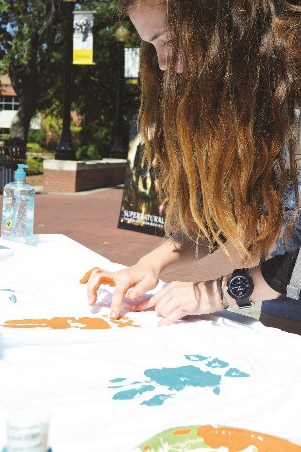 "Junior, Biological Science major, Chloe Webb signs her sorority letters on the ""These Hands Don't Haze"" sheet that was made for National Hazing Prevention Week Sept 21- Sept 25th 2015. Jillian Rodriguez / Student Printz"