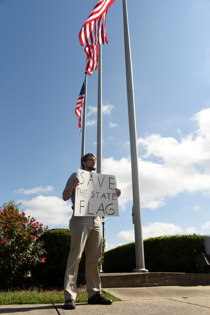 Isaac Hitt, a senior Computer Science major from Columbia, Ms, holds a sign that says 'Save the State flag' after the University of Southern Mississippi removes the Mississippi State flag from its campus on Oct 28, 2015. The University of Southern Mississippi becomes the second University in Mississippi to remove the flag from the campus. Courtland Wells/Student Printz