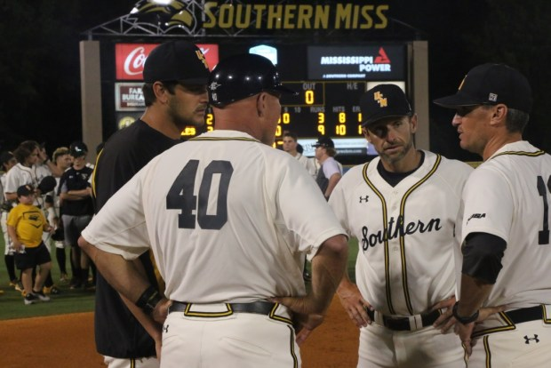 The Southern Miss coaching staff huddles together after their 9-3 victory over Marshall on May 27.