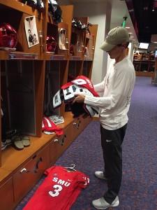 Student equipment manager John Fraser pulls quarterback Ben Hicks' jersey over his shoulder pads.