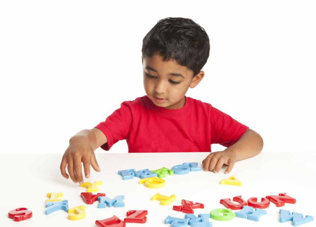 boy playing with magnet letters