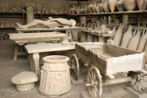 Corps pétrifié d'une victime de l'irruption du Vésuve à Pompei (79 ap. J.C.), ainsi que différents objets de l'époque, également statufiés.