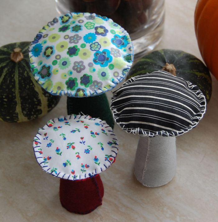 3 paddenstoelen gemaakt van vilt  en stof tussen de pompoenen en kastanjes van de herfsttafel - studio paars