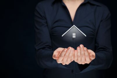 donna che tiene tra le mani una piccola casa concetto dimora
