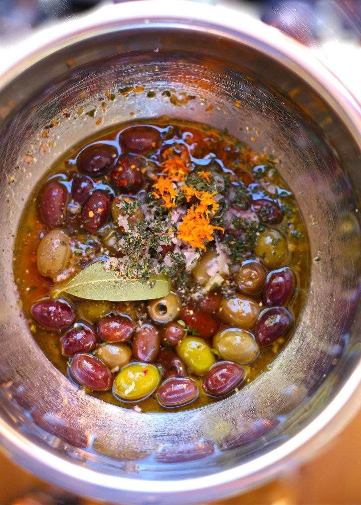 Festive Party Olives in a silver bowl with orange zest and bay leaf