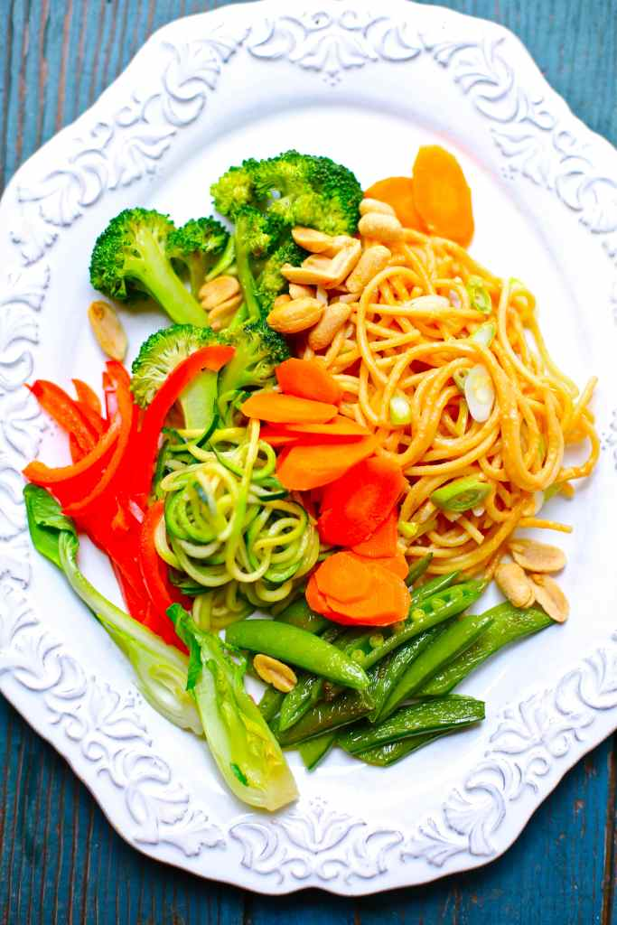 broccoli, red peppers, spiralized zucchini, peas and carrots and noodles on a white plate
