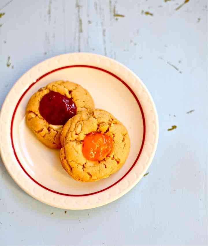 Two peanut butter and jam cookies on a white plate with red stripe, one cherry, one apricot
