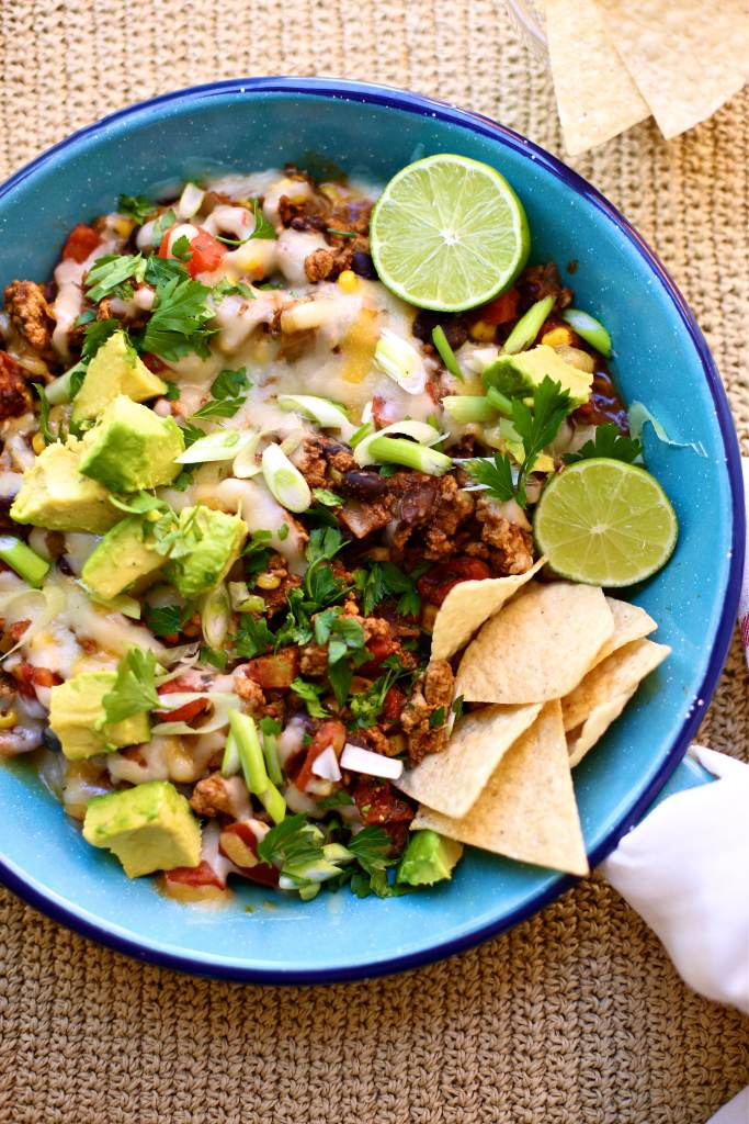 Taco Skillet Bake in a blue fry pan with chips and limes