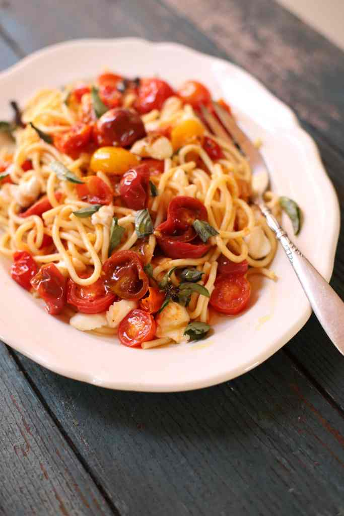 Summer Pasta with spaghetti, mozarella, tomatoes, and fresh basil on a bklue table