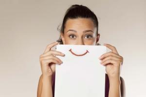 Immagine di ragazza che nasconde il sorriso dietro un foglio di carta