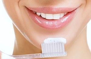 Immagine inerente il mal di denti raffigurante una donna con spazzolino e dentifricio