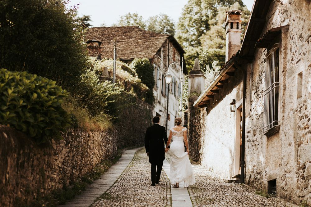 Bride and Groom walking through the streets of Orta San Giulio by © italy wedding photographer