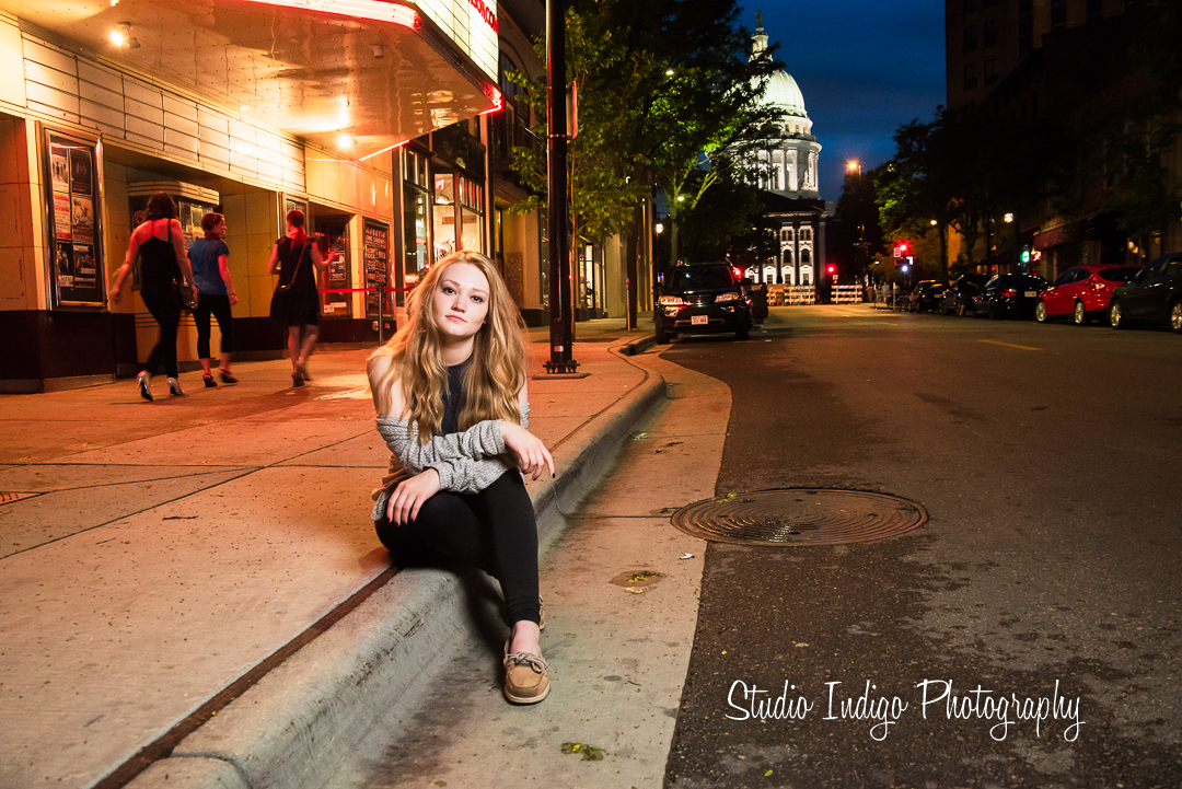 Serena in a sitting pose outside the Majestic theater in downtown madison.  Stylish senior portrait using off camera flash with a chimera softbox balanced with natural light from the theater marquee and the state capital in the backgrouind.