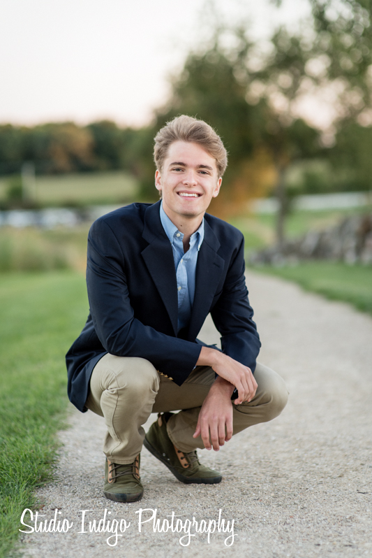 We like to keep all our posing natural and matching the personality of the hgih school senior. In this shot, Madison West senior Henry is posing in a crouched position with a suit jackeet but no tie. Love the relaxed and natural smile in this senior portrait.
