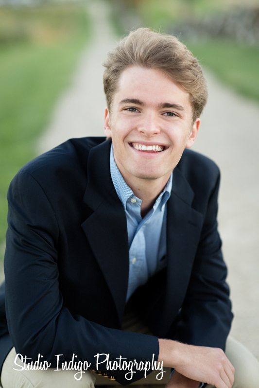 Natural smile and relaxed crouching pose in this senior portrait at pope farm park in Madison. Henry is a senior at West and wanted his senior portraits done at pope farm park. It was a gorgeous night and this shot was captured right at golden hour.
