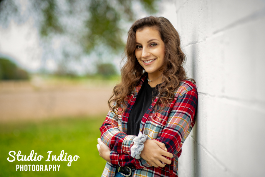 senior yearbook picture of girl in red flannel leaning against a wall