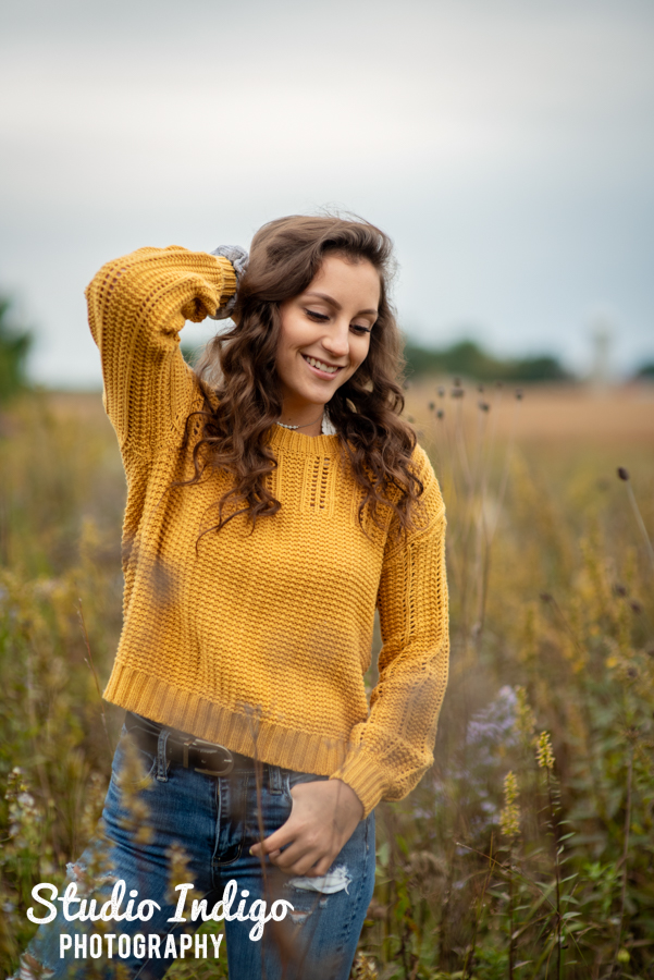 portrait of a smiling high school senior girl standing in a field of wildflowers