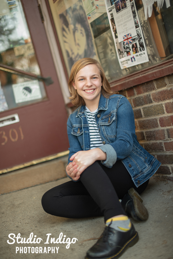 Senior picture of girl sitting outside b-side records in Madison