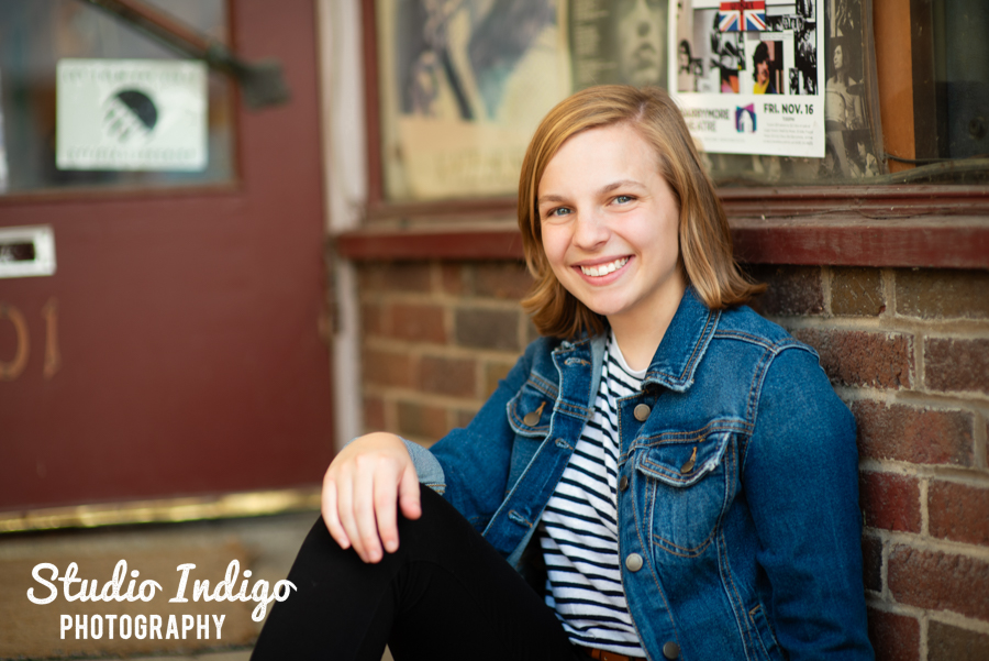 high school senior picture of girl sitting against a wall in front of b-side records in Madison.