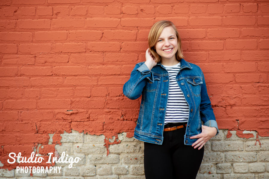 HIgh school senior portrait of girl in jean jacket standing against an orange wall