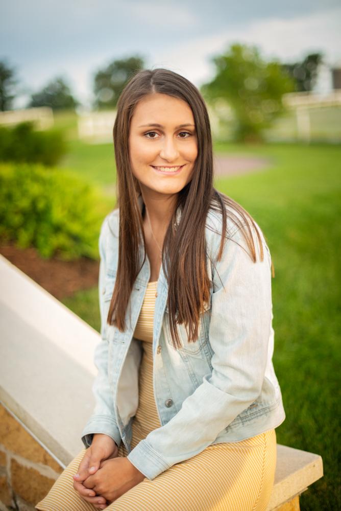 High school senior picture of girl sitting in garden wearing a jean jacket