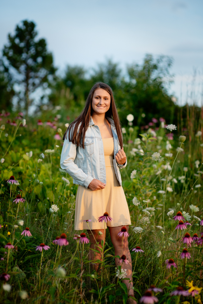 High school senior portrait of girl standing in field of wildflowers