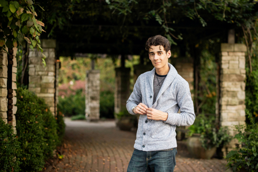 Standing senior portrait of guy wearing sweater under trellis at olbrich gardens