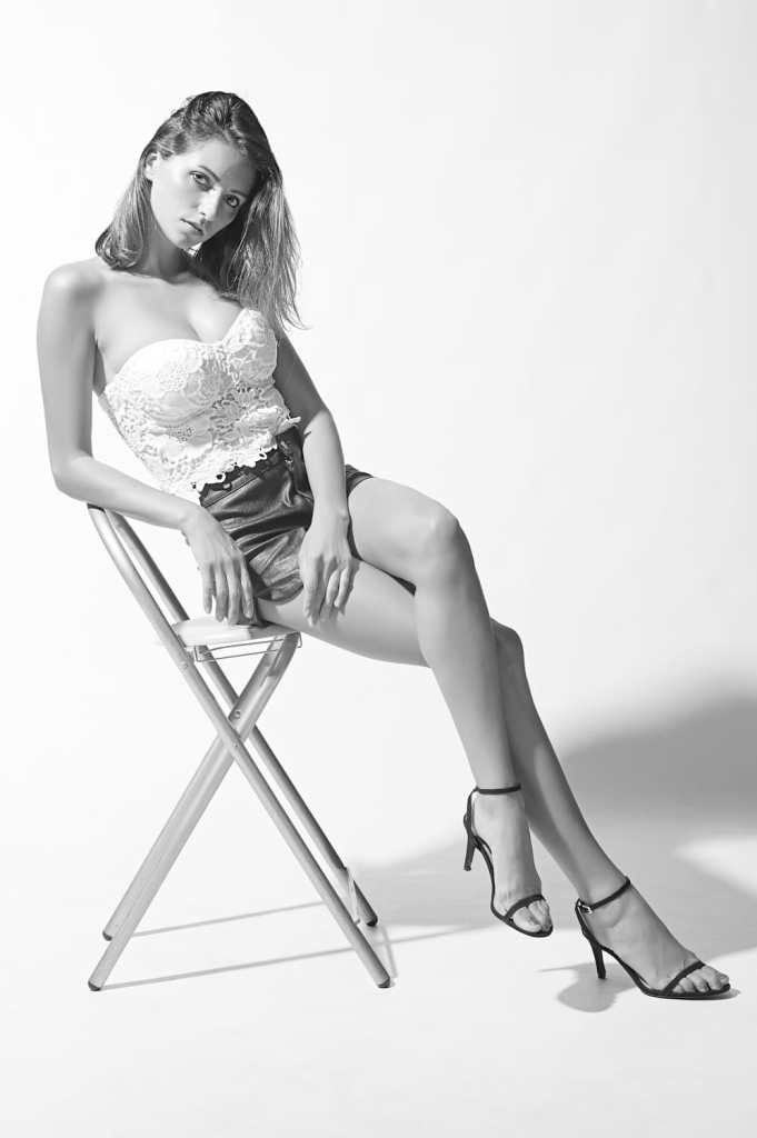 Sentarse de espaldas en una silla no suele llevar a una foto dinámica o cautivadora. La mejor modelo posa mientras está sentada puede dividirse en dos familias: inclinada hacia adelante y hacia atrás. Aquí veremos ambas y daremos algunos ejemplos de cada una. Tal vez más que con las poses de pie, estar sentado transmite más significado y emoción al espectador. Lo que se hace con los hombros, el torso y las piernas cambia drásticamente la vibración de cada imagen.