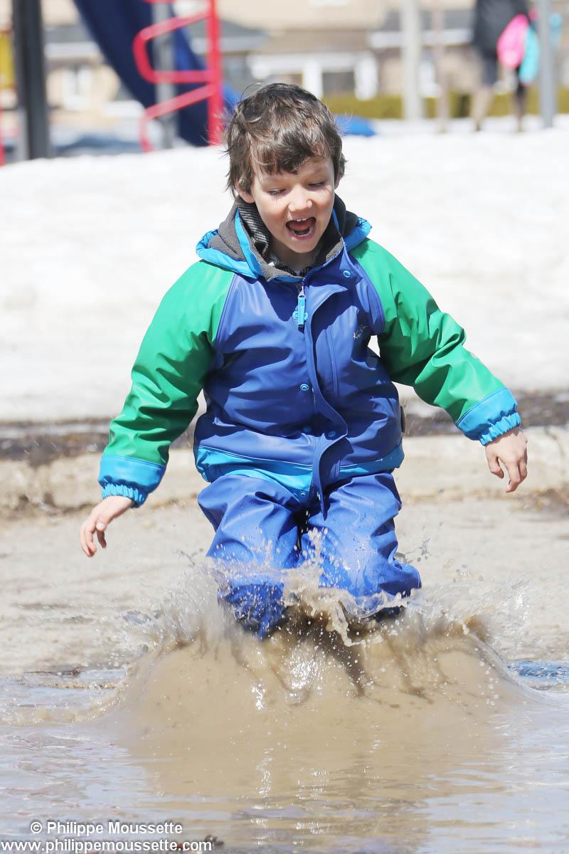 Enfant avec imper qui saute dans une marre de bouette