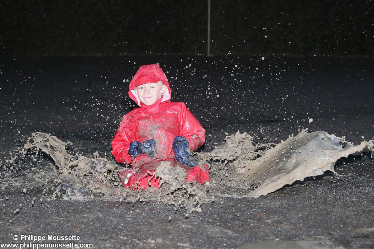 Enfant vêtu d'un imper rouge dans la bouette