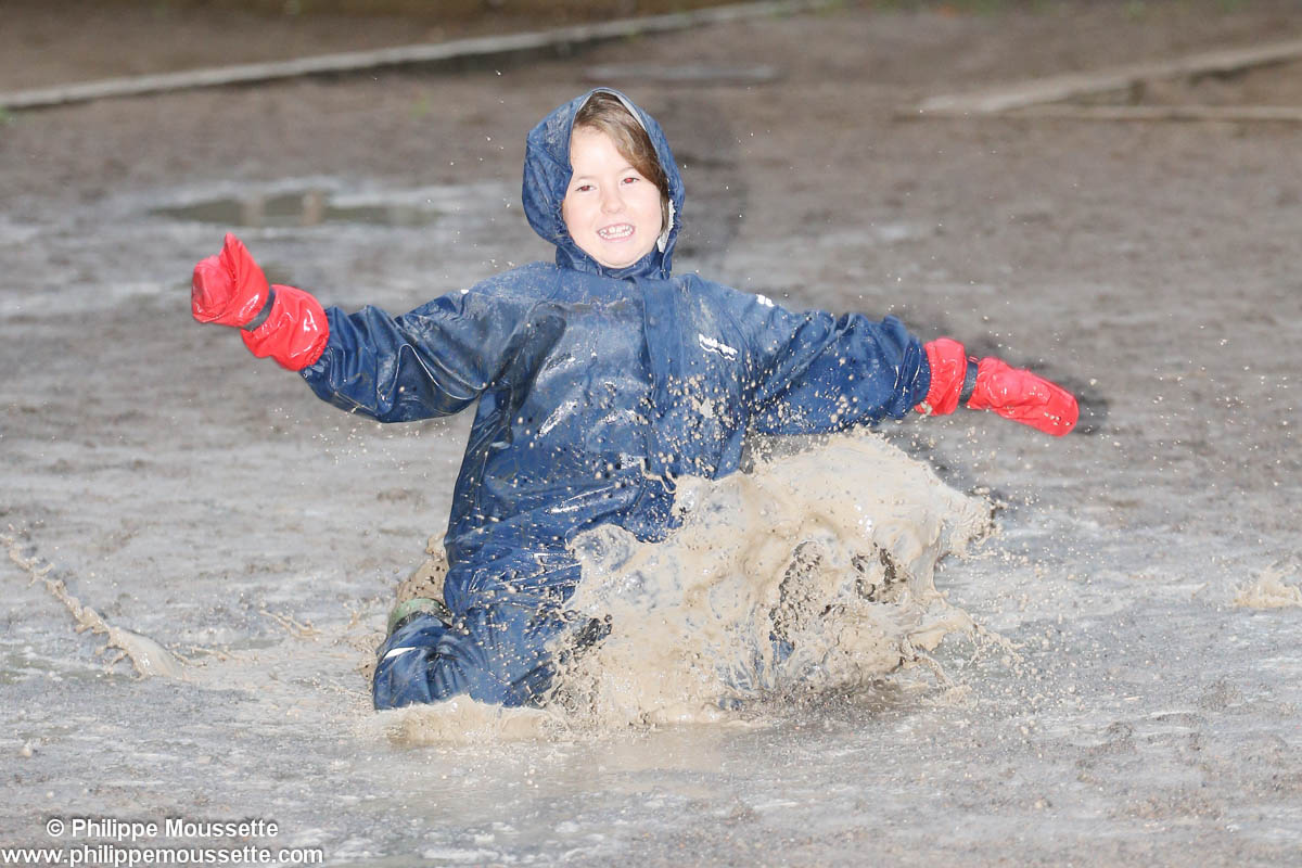 Enfant avec imper qui saute dans une marre de boue