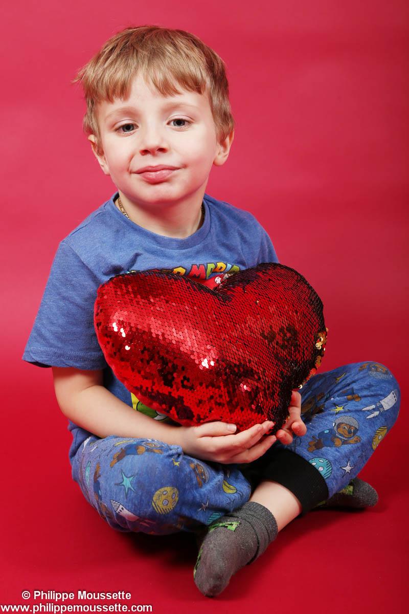 Garçon assis avec un coussin en forme de coeur