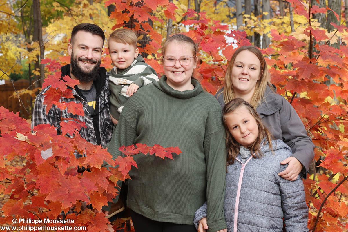 Famille derrière des arbres à l'automne