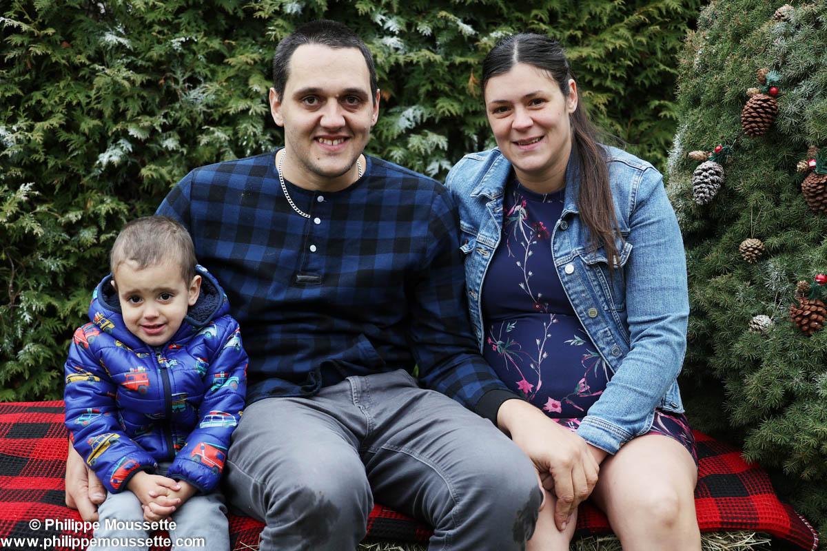 Couple avec leur fils assis devant des sapins