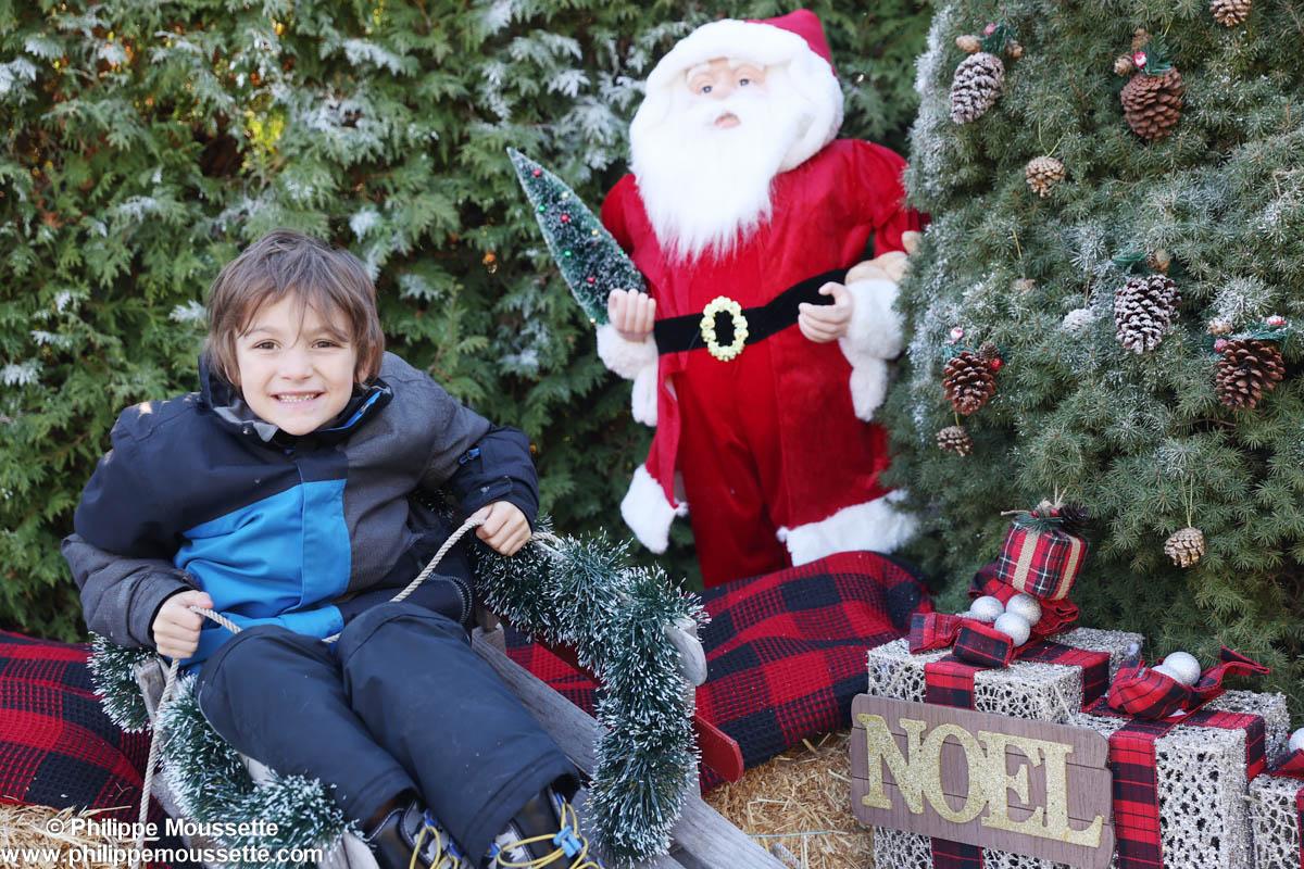 Enfant dans une luge avec un père Noël