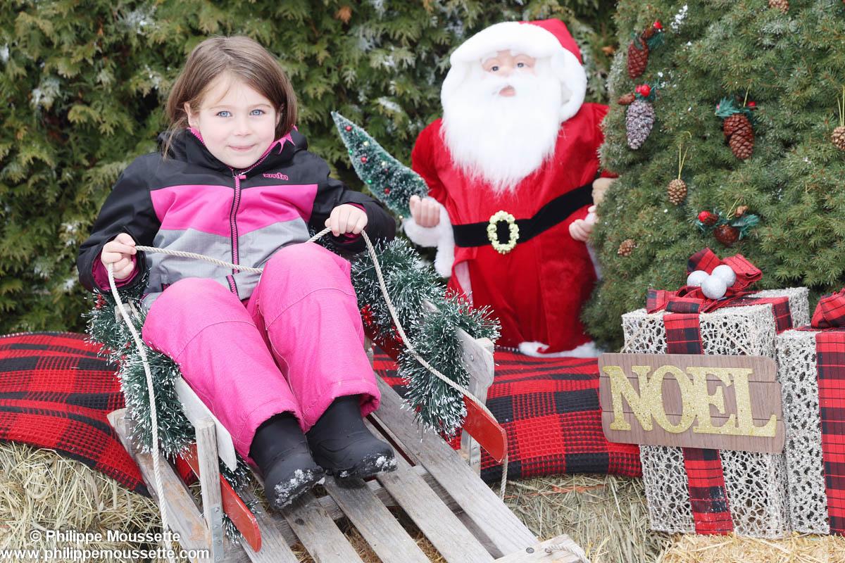 Fille assise sur une luge dans un décor de Noël