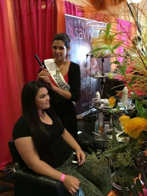 Victoria Sexsmit creates curls on a patron planning her wedding hair design at the San Diego Wedding Party Expo.