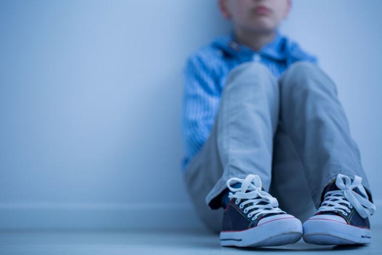 Sad boy sits alone