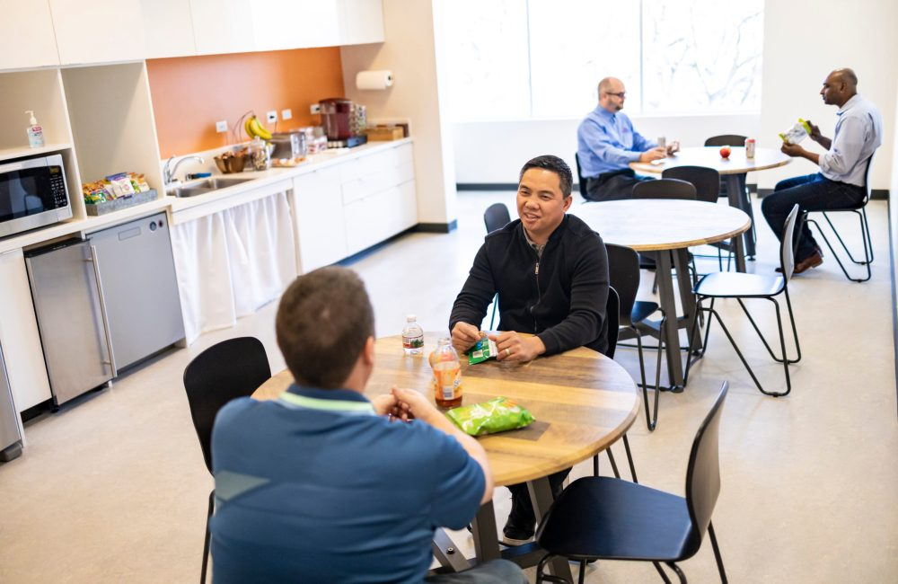 The Studio Coworking members socializing in a common area at the Creekside location.