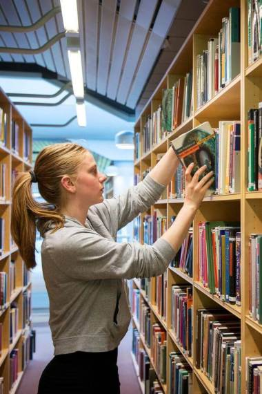 female student picking book from library shelf