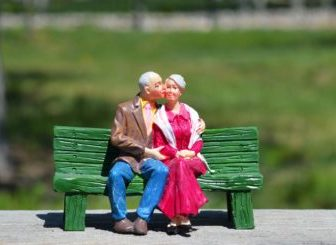 Figurines of older couple on bench