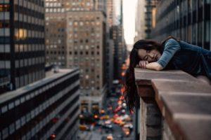 Woman sleeping on balcony ledge