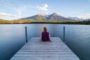 Woman sitting on dock looking out at mountains
