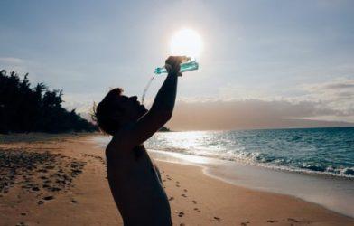 Man drinking water on beach in hot sun