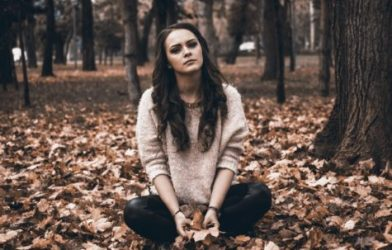 Upset young woman sitting in leaves