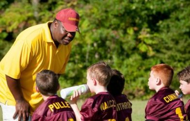 Coach talking to youth football team