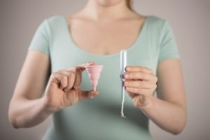 Woman holding tampon, menstrual cup