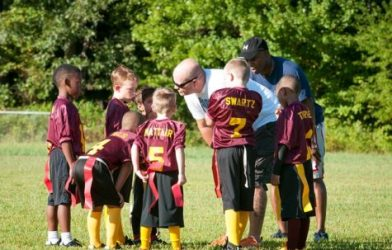 Coaches talking to youth football team